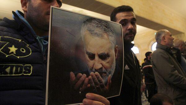 Мужчины держат фотографию генерала Касема Солеймани, убитого во время авиаудара США в Багдаде, фото из архива - Sputnik Азербайджан