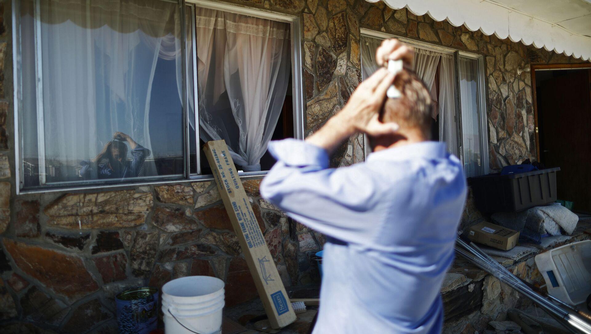 Мужчина расчесывает волосы, используя окно как зеркало, фото из архива - Sputnik Azərbaycan, 1920, 11.08.2021