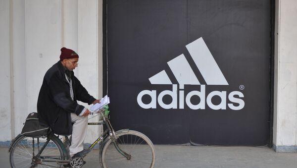 Мужчина едет на велосипеде перед логотипом Adidas, фото из архива - Sputnik Азербайджан