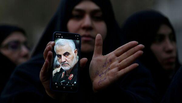 Женщина показывает фотографию убитого генерала Ирана Касема Сулеймани - Sputnik Азербайджан