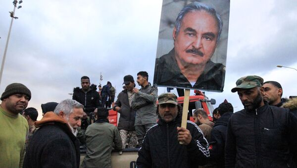 Люди поднимают фотографию ливийского силовика Халифы Хафтара - Sputnik Азербайджан