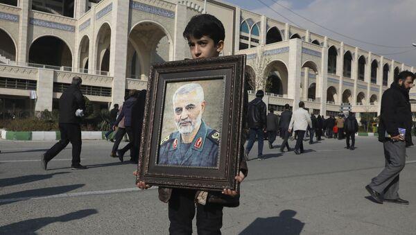 Мальчик несет портрет Касема Сулеймани, убитого во время авиаудара США в Ираке - Sputnik Азербайджан