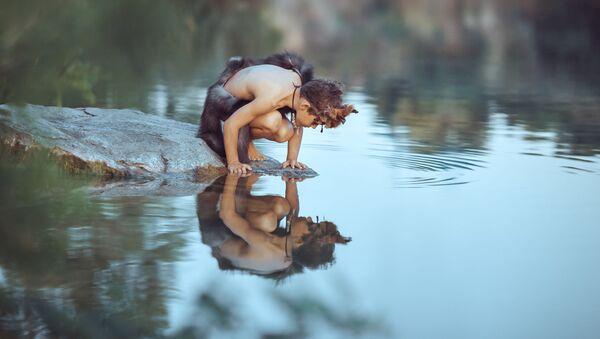 Пещерный мальчик на камне у воды - Sputnik Azərbaycan