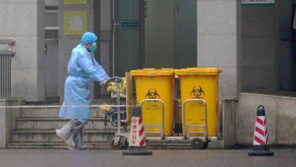 Персонал перемещает контейнеры с биологическими отходами около входа в медицинский центр в китайском городе Ухань, фото из архива - Sputnik Azərbaycan
