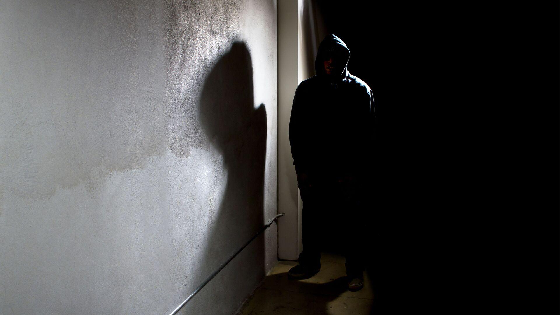 Мужчина в капюшоне прячется в тени улицы - Sputnik Азербайджан, 1920, 01.09.2021