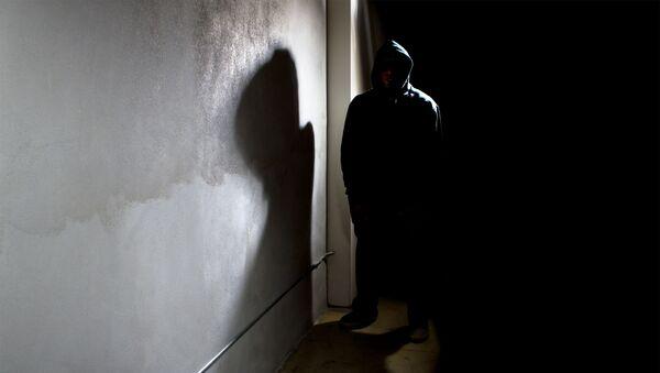 Мужчина в капюшоне прячется в тени улицы - Sputnik Азербайджан