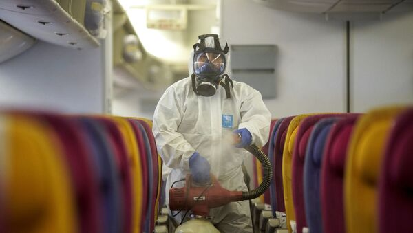 Член экипажа дезинфицирует кабину воздушного судна, 28 января 2020 года - Sputnik Азербайджан