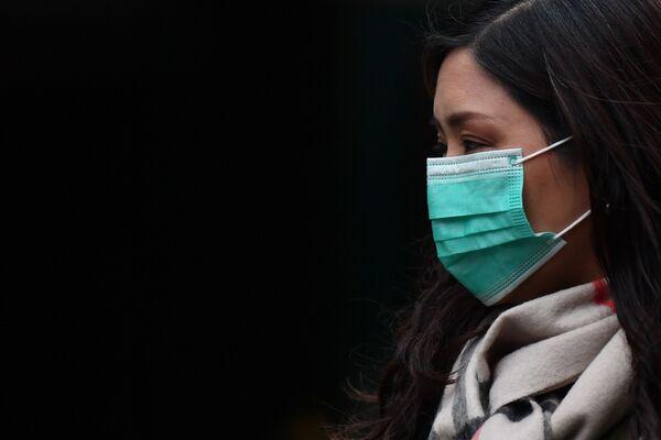 Девушка в медицинской маске в районе Чайна-таун в Лондоне - Sputnik Азербайджан