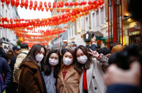 Люди в медицинских масках во время празднования Китайского нового года в районе Чайна-таун в Лондоне - Sputnik Азербайджан