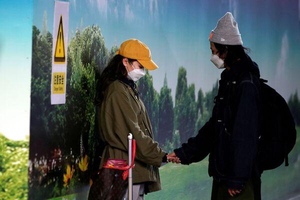 Пара в медицинских масках в аэропорту Пудун в Шанхае - Sputnik Азербайджан