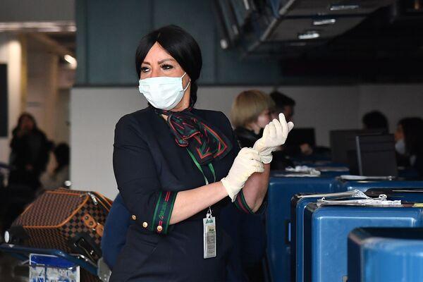 Сотрудница аэропорта в маске и перчатках до проверки пассажиров в Риме  - Sputnik Азербайджан