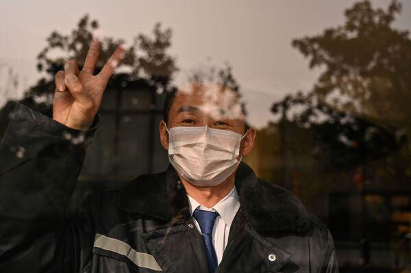 Охранник отеля в маске в китайском городе Ухань  - Sputnik Азербайджан