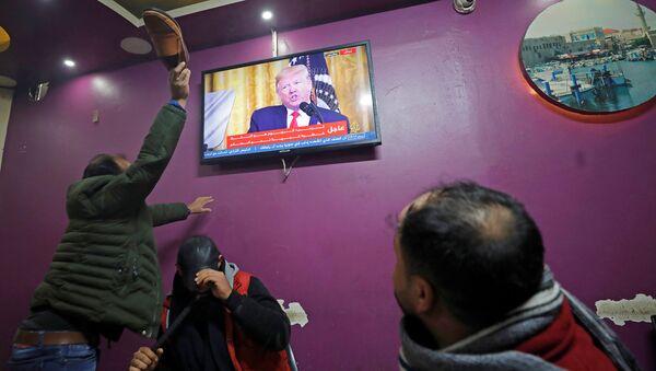 Палестинский мужчина с обувью в руке во время трансляции объявление президента США Дональда Трампа о мирном плане на Ближнем Востоке - Sputnik Азербайджан