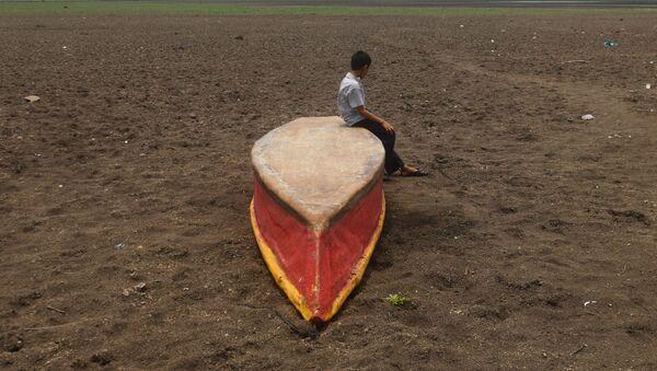 Мальчик с лодкой около озера Атескатемпа в Гватемале, высохшего в результате засухи - Sputnik Азербайджан