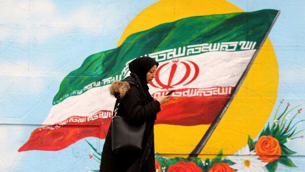 Женщина проходит перед фреской, на которой изображен иранский национальный флаг, фото из архива - Sputnik Азербайджан