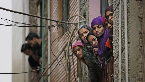 Индийские мусульманки выглядывают в окно, когда сотрудники службы безопасности патрулируют улицу в Нью-Дели - Sputnik Azərbaycan