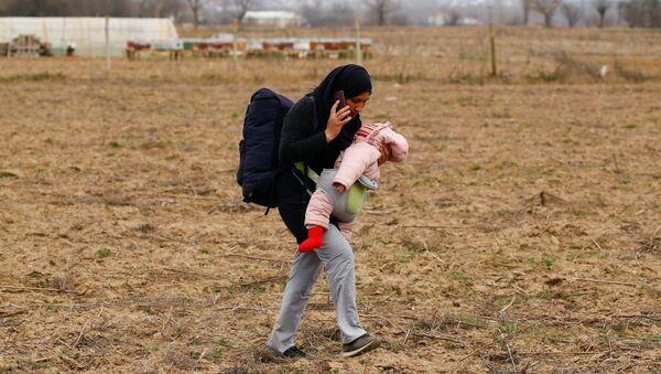 Мигрантка с ребенком на руках идет к пограничному переходу Пазаркуле в Турции - Sputnik Азербайджан