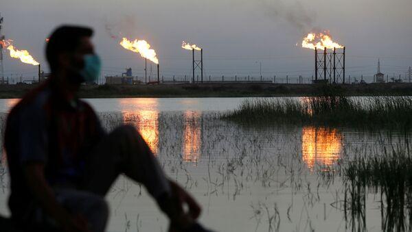 Человек в маске рядом с нефтяными качалками, фото из архива - Sputnik Азербайджан