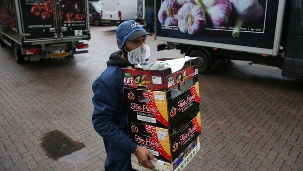 Рабочий разносит ящики со свежими фруктами и овощами, фото из архива - Sputnik Азербайджан