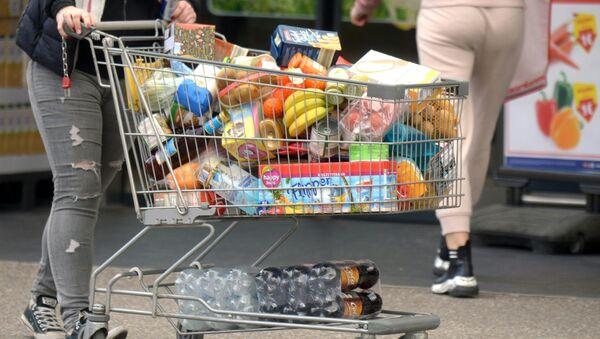 Покупатель с тележкой, наполненной продуктами в супермаркете - Sputnik Азербайджан