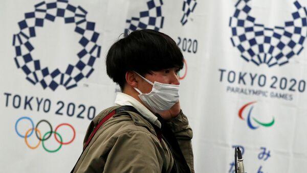 Человек на фоне олимпийской символики в Токио - Sputnik Азербайджан