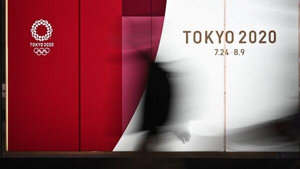 Человек на фоне олимпийской символики в Токио, фото из архива - Sputnik Азербайджан