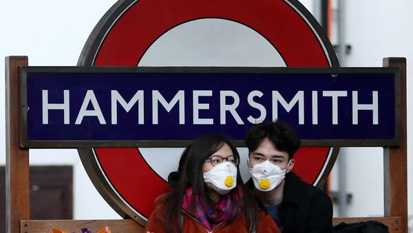 Пара в защитных масках у станции метро Hammersmith в Лондоне - Sputnik Азербайджан