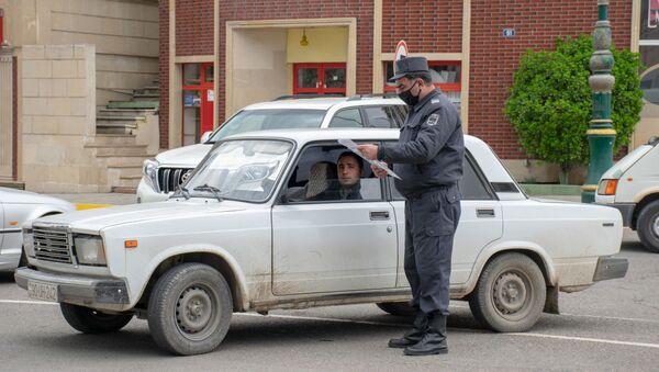 Ağstafada polis əməkdaşı sürücünün xüsusi rejim zamanı fəaliyyət göstərməsinə icazə verən sənədi yoxlayır - Sputnik Азербайджан