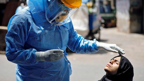 Доктор в защитном костюме тестирует девушку на коронавирус в Ахмедабаде, Индия - Sputnik Azərbaycan