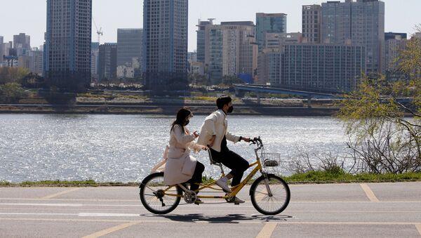 Пара в защитных масках катается на велосипеде в Сеуле, фото из архива - Sputnik Азербайджан