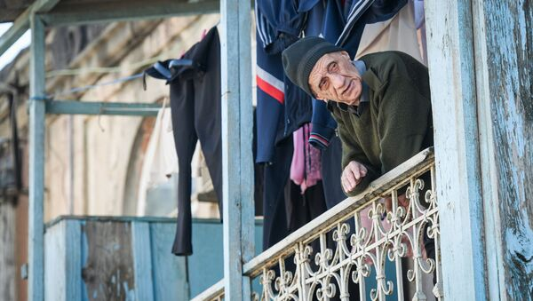 Пожилой мужчина на одном из балконов дома в Баку - Sputnik Азербайджан