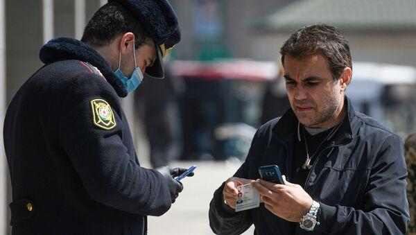Сотрудник полиции в медицинской маске проверяет документы у мужчины в Баку - Sputnik Азербайджан