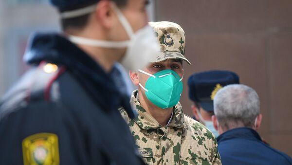 Военнослужащий и сотрудник полиции в медицинских масках на улицах Баку - Sputnik Азербайджан