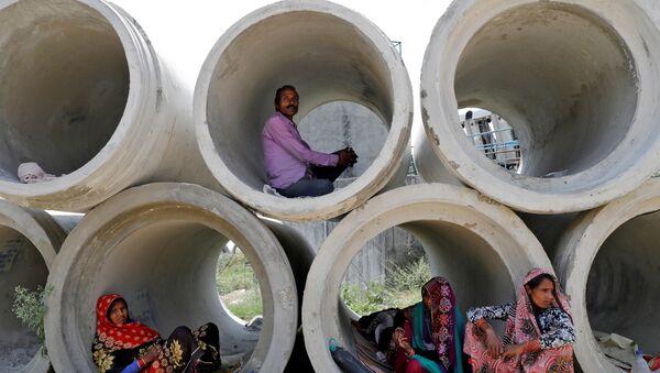 Рабочие-мигранты отдыхают в цементных трубах в Индии - Sputnik Азербайджан
