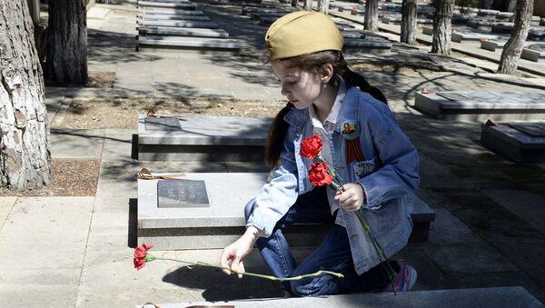 Девочка возлагает цветы к военному мемориалу в Баку - Sputnik Азербайджан