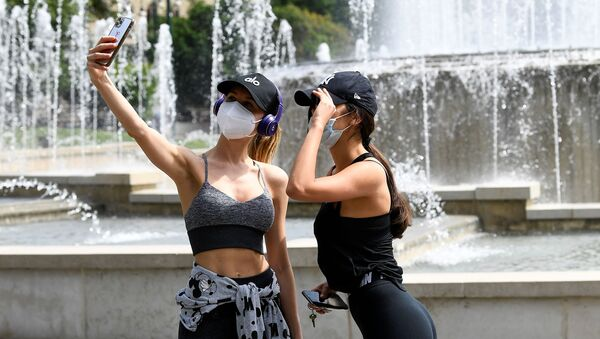 Девушки в медицинских масках делают селфи на фоне фонтана на площади Кастелло в Милане - Sputnik Azərbaycan