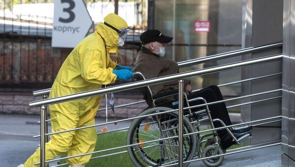 Медик транспортирует пациента с подозрением на коронавирусную инфекцию в Москве - Sputnik Азербайджан