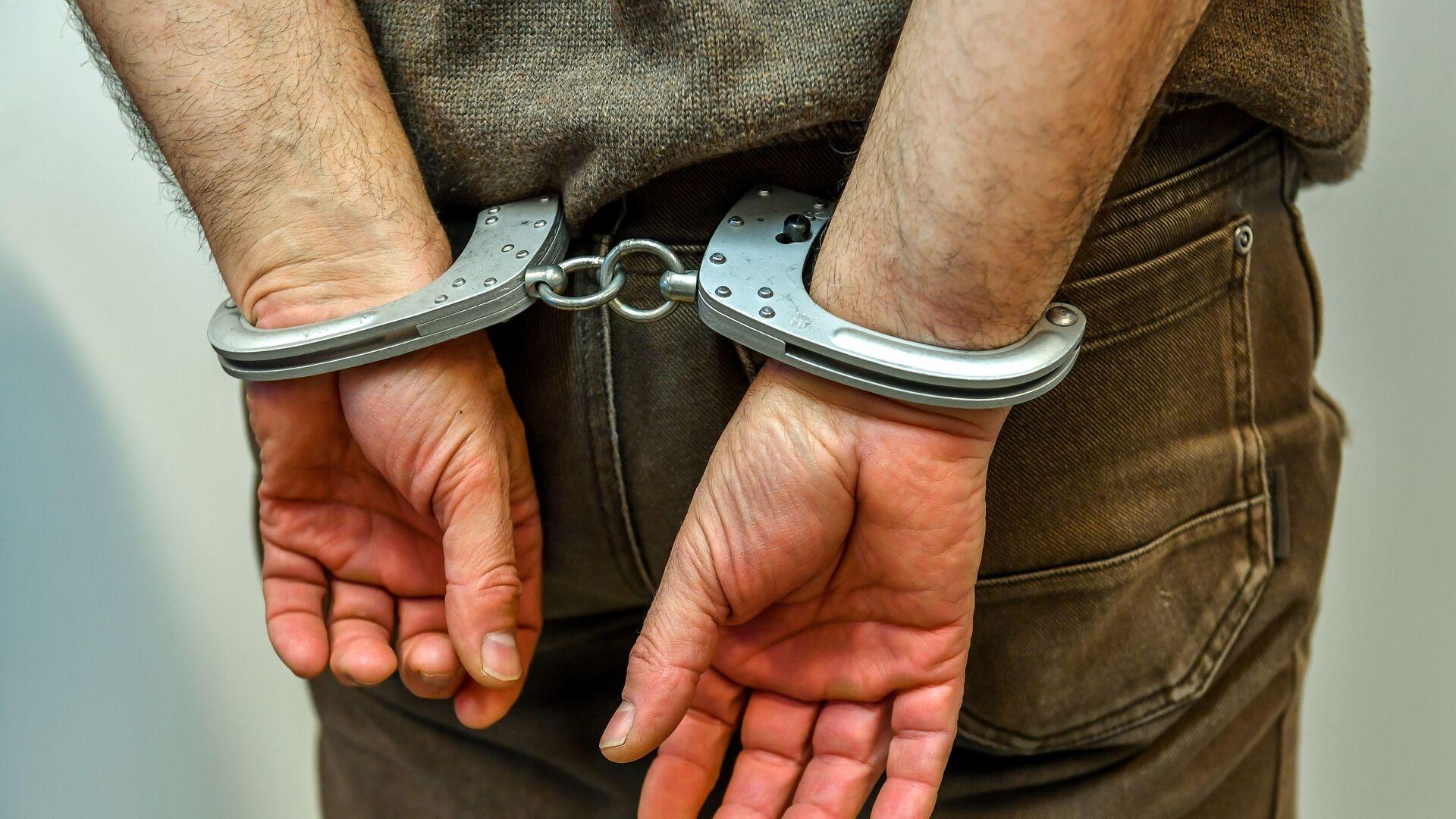 Мужчина в наручниках в полицейском участке, фото из архива - Sputnik Azərbaycan, 1920, 10.09.2021