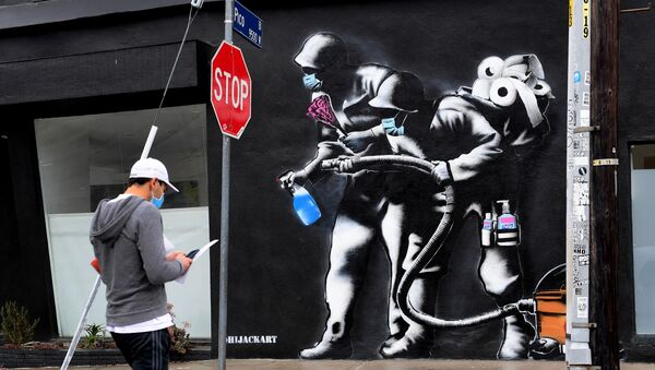 Прохожий напротив граффити, посвященного борьбе с коронавирусом, в Лос-Анджелесе - Sputnik Азербайджан