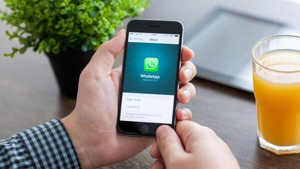 Мужчина держит смартфон iPhone 6 с WhatsApp на экране - Sputnik Azərbaycan