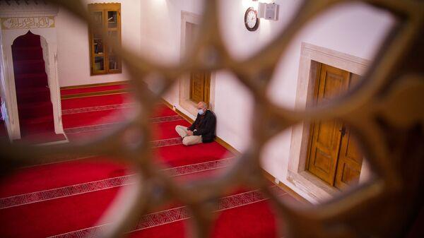 Верующий в защитной маске ждет начала пятничной молитвы, фото из архива - Sputnik Азербайджан