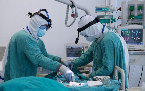 Медицинские работники проводят малоинвазивную процедуру в отделении реанимации и интенсивной терапии госпиталя COVID-19 в ГКБ No1 имени Н.И. Пирогова в Москве - Sputnik Азербайджан