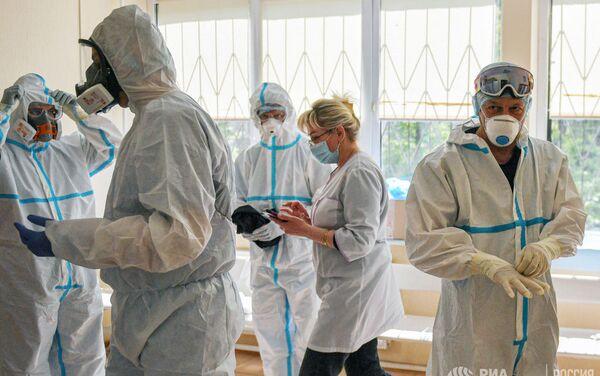 Медики надевают костюмы в зеленой зоне перед началом работы с зараженными COVID-19 пациентами в Университетской клинической госпитале №2 Первого Московского государственного медицинского университета имени И. М. Сеченова - Sputnik Азербайджан