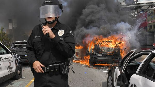 Полицейский Лос-Анджелеса на фоне горящей машины во время протестов  - Sputnik Азербайджан