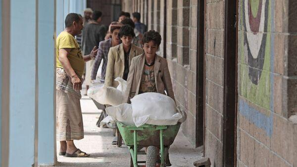 Йеменцы получают продовольствие, предоставленное Всемирной продовольственной программой, в школе в Сане, Йемен - Sputnik Азербайджан