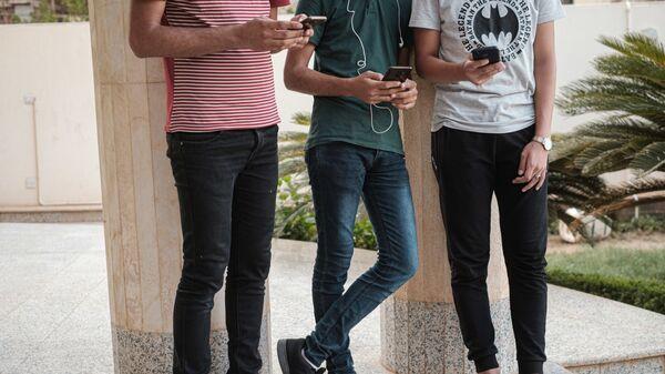 Молодые люди со смартфонами в руках, фото из архива - Sputnik Azərbaycan