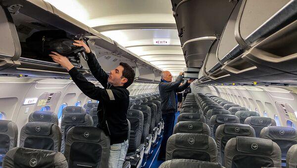 Пассажиры с ручной кладью в самолете, фото из архива - Sputnik Азербайджан