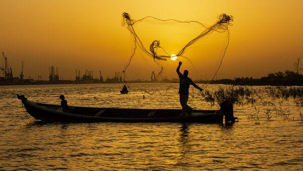 Рыбак закидывает сеть на закате на реке Шатт-эль-Араб в иракском городе Басра - Sputnik Азербайджан