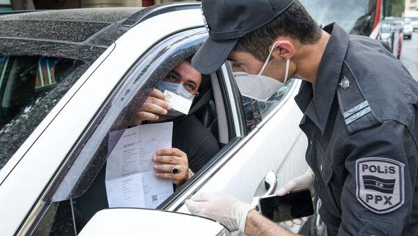 Сотрудник полиции проверяет разрешение водителя для выходы на улицу - Sputnik Азербайджан