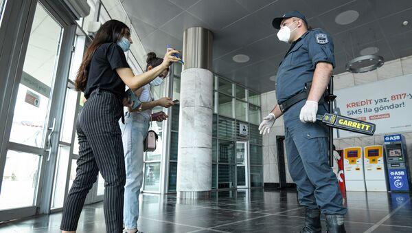Девушка показывает сотруднику полиции разрешение для выхода на улицу  - Sputnik Азербайджан